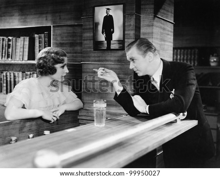 Man and woman standing together at a bar counter and talking
