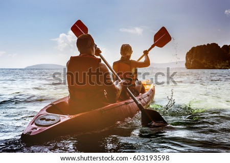 Man and woman swims on kayak in the sea on background of island. Kayaking concept