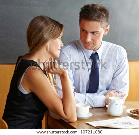 Man and woman talking in a caf�© while having a cup of coffee