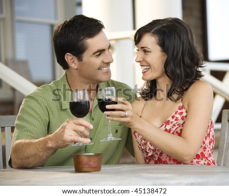 Man and woman toast with red wine glasses at an outdoor cafe. Horizontal shot.
