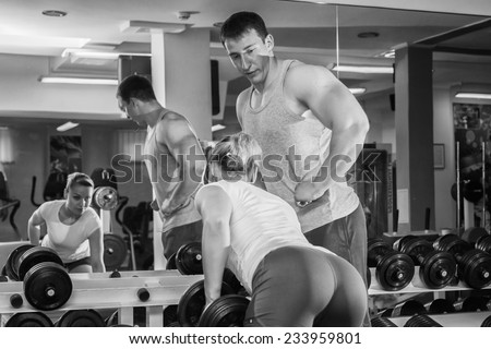 Man and woman trained in the gym. Trainer demonstrates exercises, girl. Loving couple in the gym. Family fitness, exercise, coaching - team work in the gym.