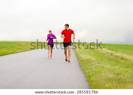 Man and woman two people runners running on country road, healthy fitness lifestyle, sport speed training beautiful landscape. Young couple doing workout exercising walking outdoors in nature.