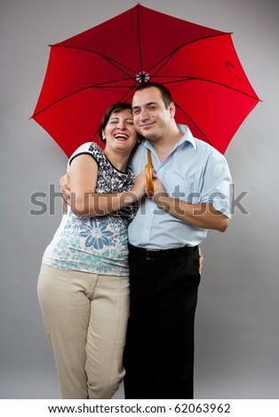 Man and woman under red umbrella, studio shot