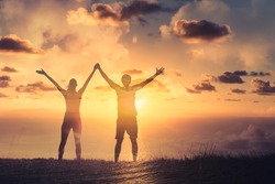 Man and woman united as a team holding hands with arms up to the sky. Victory, and strength concept.