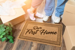 Man and Woman Unpacking Near Our First Home Welcome Mat, Moving Boxes and Plant.