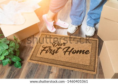 Man and Woman Unpacking Near Our First Home Welcome Mat, Moving Boxes and Plant. Foto stock ©