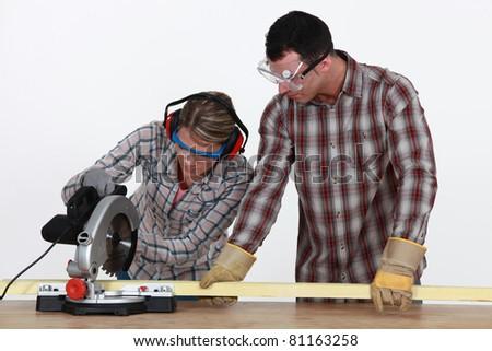 Man and woman using circular saw