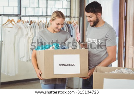 Man and woman volunteers with box standing in creative office