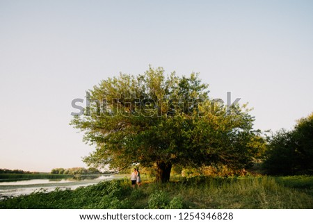 Man and woman walk in the woods by the river