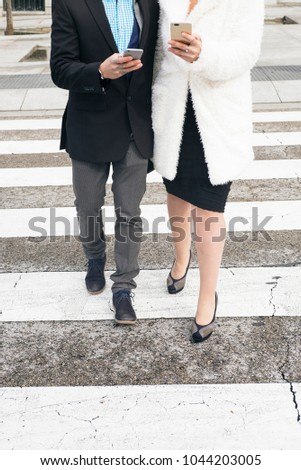 Man and woman walking on the zebra crossing with smartphone #1044203005