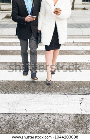 Man and woman walking on the zebra crossing with smartphone #1044203008