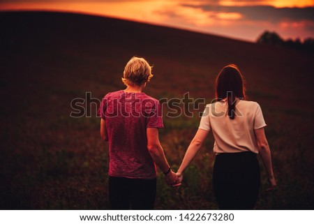 Man and woman walking together in summer sunset light, dark photo, edit space #1422673280