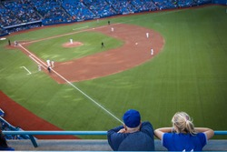 Man and woman watching a baseball game on the opening pitch