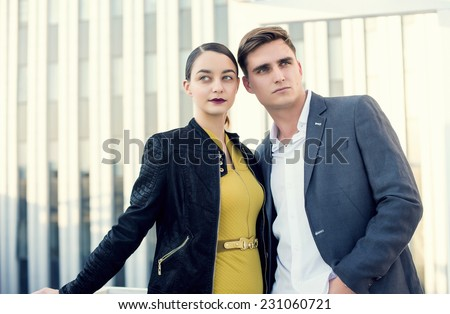 Man and woman wearing classic clothes, him in white shirt and grey jacket, her in yellow dress with leather jacket standing together with the business center on the background.