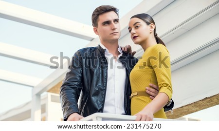 Man and woman wearing classic clothes, him in white shirt and leather jacket, her in yellow dress jacket standing together with the business center on the background. Outdoor fashion shot.