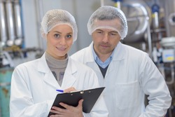 Man and woman wearing hair nets making notes on clipboard