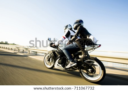 Man and woman wearing leather jackets and stylish sunglasses riding on motorcycle