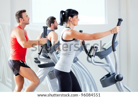 man and woman with elliptical cross trainer in sport fitness gym club - stock photo