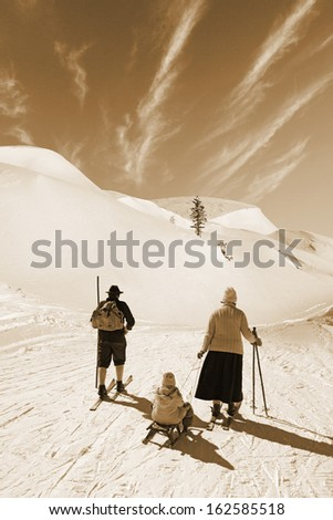 Man and woman with old wooden skis and child on sled on snowy mountain