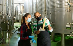 Man and woman workers of winery in protective masks checking wine production process at fermentation tank