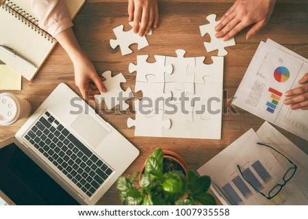 Man and woman working in the office. Collaborative teamwork. People are trying to connect couple puzzle piece. Symbol of association and connection. Concept of business strategy. #1007935558