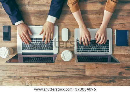 man and woman working on their computers. the view from the top. two laptops, two persons.