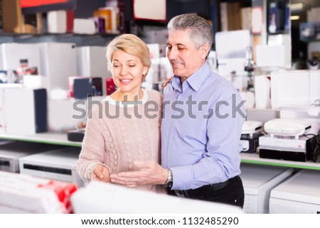 Man and woman 48-56 years old are visiting shop of household appliances for survey of goods for kitchen and house.  #1132485290