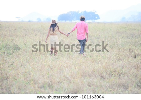 man and women holding hand and walking in grass field