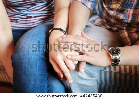 man and women holding hand together, family concept, warm feeling between man and woman sit together on sofa and hand hold for power up heart energy, serious and worry feeling