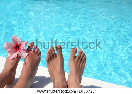 Man and women's feet by bright pool