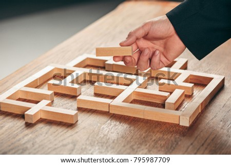 Man and wooden cubes on table. Management concept #795987709