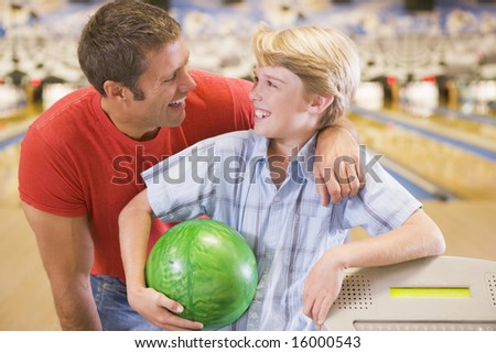 Man and young boy in bowling alley holding ball and smiling