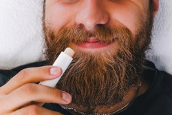 Man applying lip balm in stick on his lips. Taking care of skin concept.