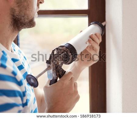 Man applying silicone sealant with caulking gun