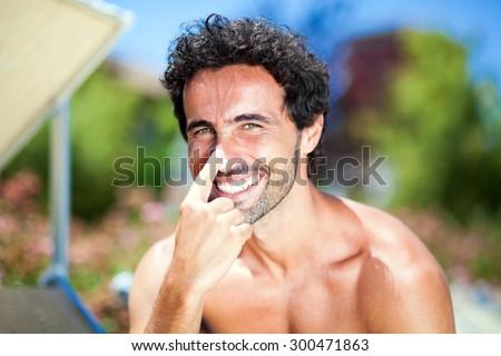 Shutterstock Man applying sun screen on his nose