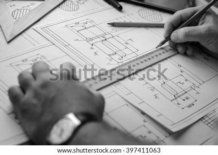 Man architect draws a plan, graph, design, geometric shapes by pencil on large sheet of paper at office desk. Soft focus. Black and white