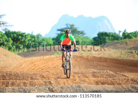 Man are riding mountain bikes uphill in a desert landscape.