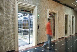 Man are walking in office past elevators door, Modern steel elevator cabins in a business lobby or Hotel, Store, interior, office,perspective wide angle.