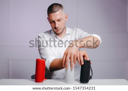 Man arranging his red, white and black wireless portable speakers on te table. The collection of gadgets. Stockfoto ©