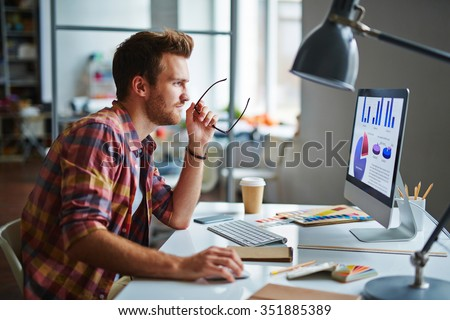 Man as a designer sitting at his table and working on computer #351885389