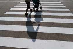 Man as a father and his baby in stroller using Zebra crossing way with clean concrete road. Light and shadow on traffic sign area and textured on cement ground. Background for safety first concept.
