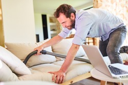 Man as a houseman vacuuming a sofa in the living room