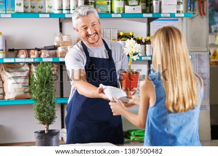 Man as florist in flower shop sells orchid and potting soil to a woman