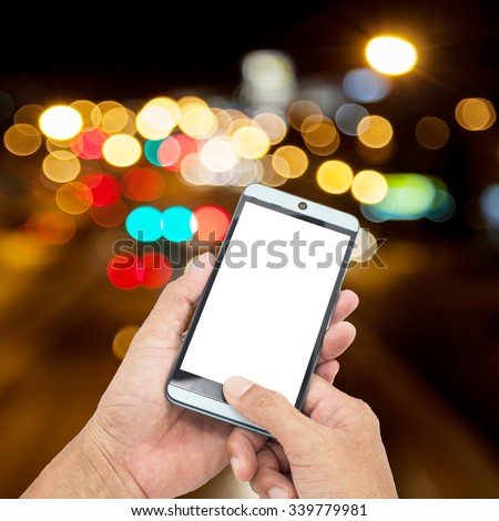 Man asia hand hold and touch screen smart phone on Blurred Defocused Lights of High way Traffic on  Phuket City Road at Night - Commuting and The beauty of the lights at night Concept