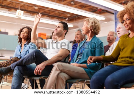 Man Asking Question At Neighborhood Meeting In Community Center