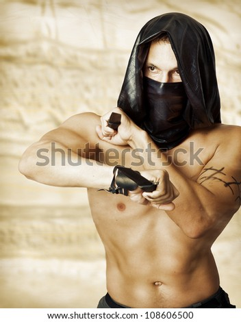 Man assassin with sexy torso in black mask and hood holding two knifes in hands