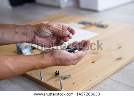 Man assembling furniture at home, male hand with wooden dowel pins and screws