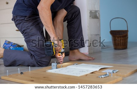 Man assembling furniture at home using a cordless screwdriver