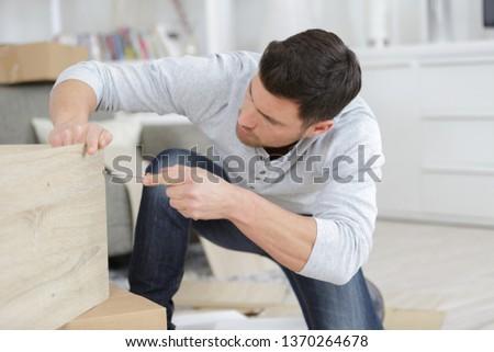 man assembling the delivered furniture