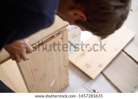 Man assembling wooden furniture at home, close up image